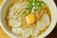 Boiled instant noodles topping egg yolk and slice fish line in spicy soup. In bowl Royalty Free Stock Photography