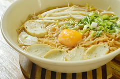 Boiled instant noodles topping egg yolk and slice fish line in spicy soup. In bowl Royalty Free Stock Image