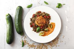 Boiled lentils with carrot puree and grilled zucchini. Colorful vegetable meatless dish stock photo
