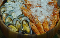 Boiled mussel and shrimp preserved with ice in wooden basin Stock Photo