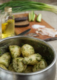 Boiled new potatoes with herbs. In a pan. Lard, rye bread and cucumber are on a cutting board Stock Photography