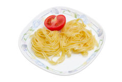 Boiled noodles and half fresh tomato on dish Stock Photo