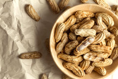 boiled peanuts in wooden cup on crumpled paper Stock Image