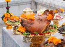 Boiled pig`s heads decorated with flowers sacrificial offering in worship. Stock Photos