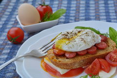 Boiled, poached egg on sandwich with meat, bread, cheese, tomato and fork on white plate on foreground. Boiled, poached egg on sandwich with meat, bread, cheese Royalty Free Stock Image