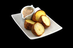Boiled potato with sauce. On a white dish isolated on a black background royalty free stock photography