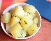 Boiled potatoes with greens in a deep red plate stock photos