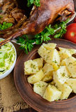 Boiled potatoes in a clay bowl, baked goose and cabbage salad. Royalty Free Stock Images