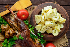 Boiled potatoes in a clay bowl  and roasted goose Royalty Free Stock Images