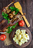 Boiled potatoes in a clay bowl  and roasted goose. Stock Photos