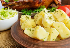 Boiled potatoes in a clay bowl  and roasted goose. Royalty Free Stock Photo