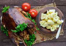 Boiled potatoes in a clay bowl  and roasted goose. Royalty Free Stock Image