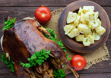 Boiled potatoes in a clay bowl  and roasted goose. Stock Photo