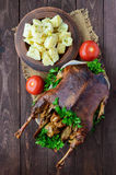 Boiled potatoes in a clay bowl  and roasted goose. Royalty Free Stock Photos