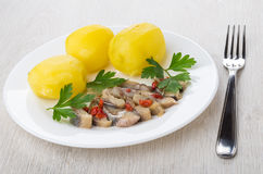 Boiled potatoes with herring in plate and fork Stock Image