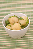 Boiled potatoes with parsley on a bamboo. Boiled potatoes with parsley on a green bamboo napkin Stock Photography