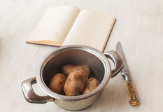 Boiled potatoes in a saucepan and book of recipes Royalty Free Stock Photos