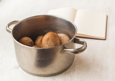 Boiled potatoes in a saucepan and book of recipes Stock Image
