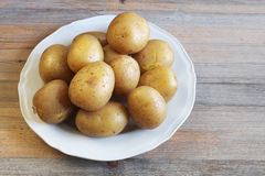 Boiled potatoes in their skins on a plate Royalty Free Stock Images
