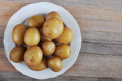 Boiled potatoes in their skins on a plate, wooden background Royalty Free Stock Images