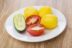 Boiled potatoes with tomato and cucumber in plate, cucumbers Royalty Free Stock Images