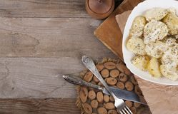 Boiled potatoes on a white plate. Dietary food. Wooden background, wooden cutlery. View from above. Boiled potatoes on a white plate. Dietary food. Wooden stock image