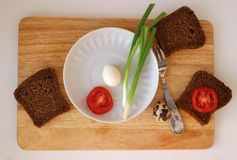 Quail egg on white saucer flat lay. Boiled Quail egg on white saucer and wholegrain bread flat lay on wooden board Stock Photos