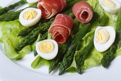 Boiled quail eggs with ham and asparagus close-up top view Stock Photos