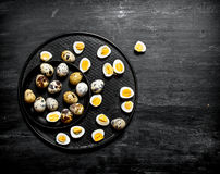 Boiled quail eggs on the plate. On a black wooden background Stock Image