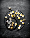 Boiled quail eggs on the plate. On a black wooden background Stock Images