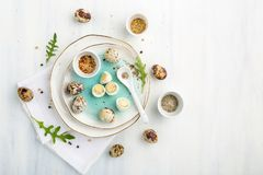 Boiled quail eggs top view. Plates with hardboiled quail eggs and ground spices and space for text Royalty Free Stock Photo