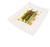 Boiled Raw Okra With Sambal III. Boiled raw okra or ladies fingers with deep fried crunched chili sambal on white plate over white background Royalty Free Stock Photo