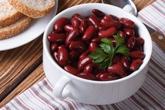 Boiled red kidney beans in bowl closeup horizontal top view. Boiled red kidney beans with parsley in white bowl closeup on the table. horizontal top view Stock Image