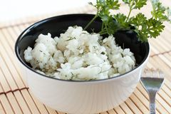 Boiled rice in black and white circular plate. Rice without the meat with dill and parsley Stock Image