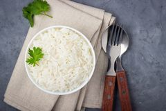 Boiled rice, cutlery and napkin on gray concrete background.  royalty free stock photography