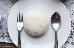 Boiled rice. Boiled rice with spoon and fork on white dish Royalty Free Stock Photo