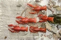 Boiled salgou lagostas vermelhas com a garrafa da cerveja em uma lona com seixos das conchas do mar Imagens de Stock Royalty Free