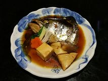 Boiled salmon head in sweet soy sauce served with carrot and tofu in a local Japanese restaurant, traditional Japanese food, main Stock Images