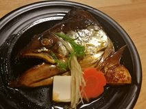 Boiled salmon head in sweet soya sauce served with carrot and tofu in a local Japanese restaurant, traditional Japanese food, Stock Photography