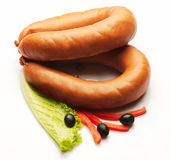 Boiled sausage decorated with red pepper, olive and salad stock image