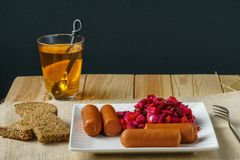 Boiled Sausages with salad on a plate a glass of tea austere breakfast. Boiled Sausages with salad on a plate a glass of tea austere breakfast royalty free stock images