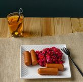 Boiled Sausages with salad on a plate a glass of tea austere breakfast. Boiled Sausages with salad on a plate a glass of tea austere breakfast royalty free stock photos