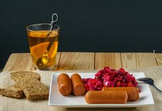 Boiled Sausages with salad on a plate a glass of tea austere breakfast. Boiled Sausages with salad on a plate a glass of tea austere breakfast royalty free stock image