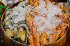 Boiled shrimp and mussel preserved with ice in wooden basin Royalty Free Stock Images