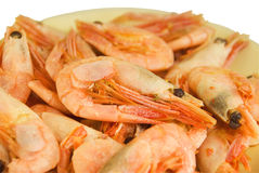 Boiled shrimps. On a yellow plate. It is isolated on a white background Royalty Free Stock Photo