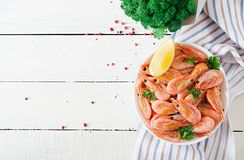 Boiled shrimps or prawns on a white bowl on a white table. Seafood. Overhead, top view, flat lay stock photo
