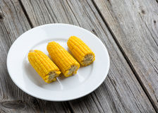 Boiled sweet corn cobs with salt on a wooden Royalty Free Stock Photo