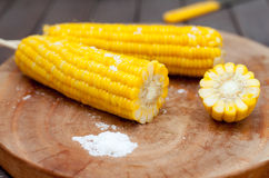 Boiled sweet corn cobs with salt on  wooden background Royalty Free Stock Image