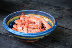 Boiled tiger shrimps in a earthenware bowl on rustic dark wood Royalty Free Stock Photography