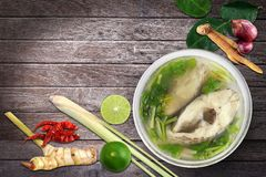 Boiled tilapia fish in clear bowl and Ingredients thai curry Top view on wooden Tom-yam-pla thai word, Piece slice fish soup. The Boiled tilapia fish in clear Royalty Free Stock Photo